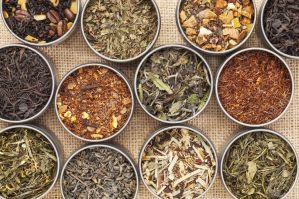 16729316-samples-of-loose-leaf-green-white-black-and-herbal-tea-in-metal-cans-on-canvas-background-Stock-Photo